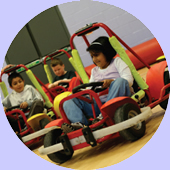Children driving around cones in the gym at Parrs Wood