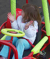 Little girl in kart clapping hands